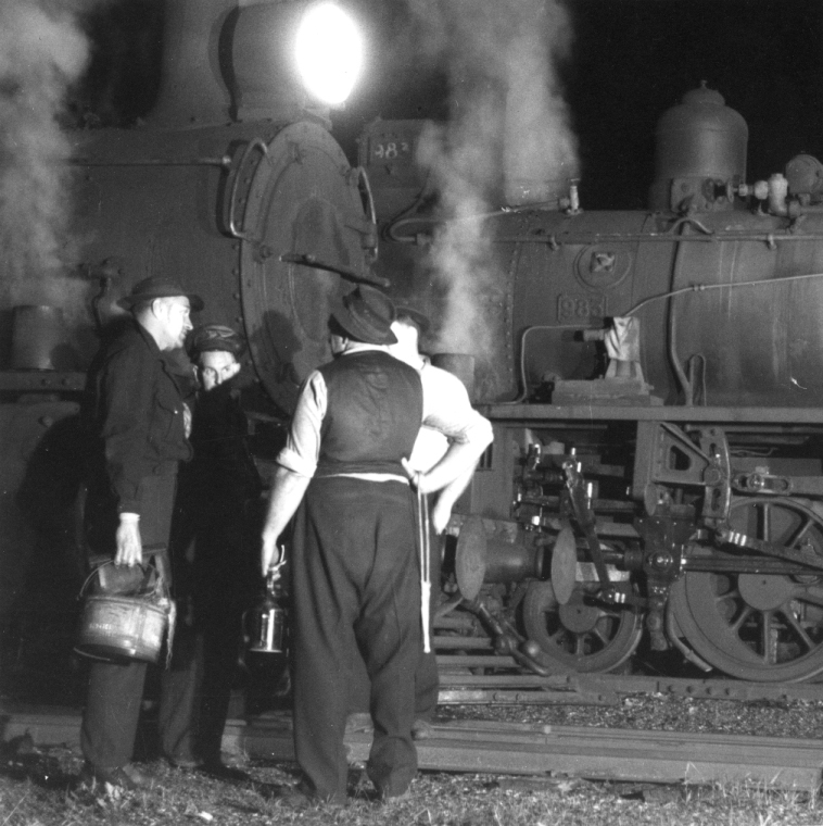 Men standing around trains chatting